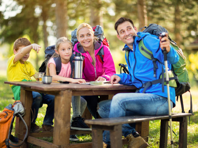 smiling family of mountaineers in forest